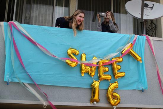 فتاة-أمريكية-تحتفل-بعيد-ميلادها--في-شرفة-شقتها