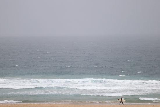راكب أمواج يسير على طول شاطئ بوندي وسط تخفيف قيود مواجهة كورونا