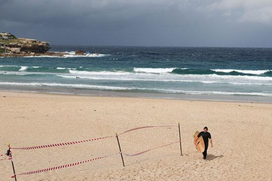 راكب أمواج يسير على طول شاطئ بوندي وسط تخفيف قيود