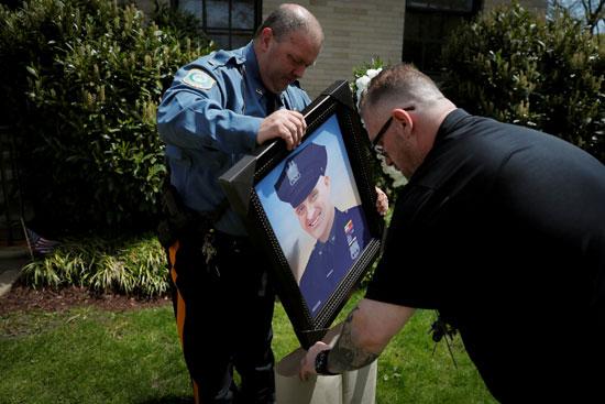 يحمل صورة الضابط المتوفى