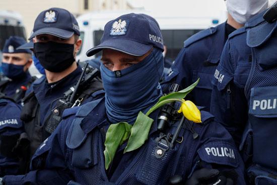 أفراد الشرطة وإحداهن تعلق وردة