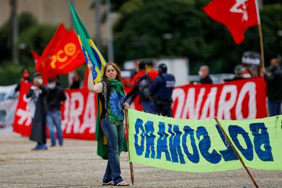 برازيلية ترفع علم بلادها أثناء الاحتجاج ضد سياسات الرئيس