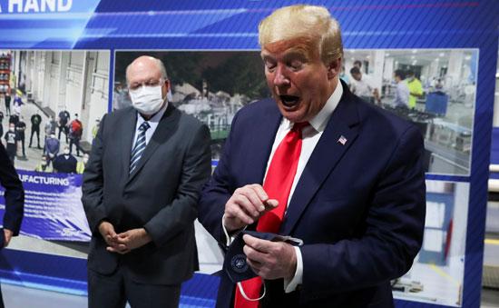 ترامب يمسك بكمامة خاصة ممهورة بالختم الجمهورى ولم يرتديها