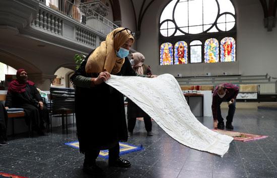 سيدة تضع المصلية داخل الكنيسة لأداء الصلاة