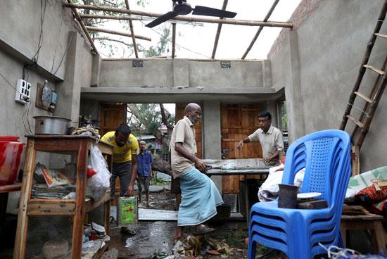 رجال ينقذون عناصر من متجر متضرر بعد أن وصل إعصار أمفان إلى اليابسة
