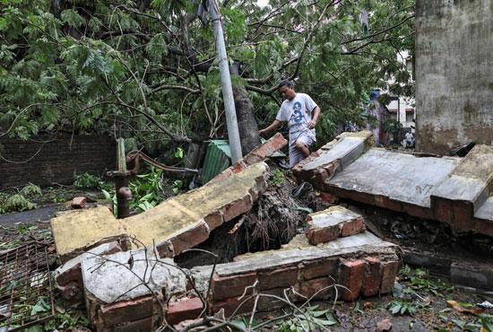 رجل يمشى على جدار ساقط بسبب اعصار امفان