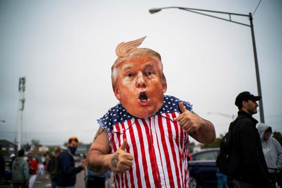 أحد المتظاهرين يرتدي قناعا على شكل ترامب