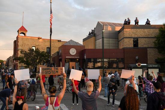 متظاهرون يرفعون لافتات