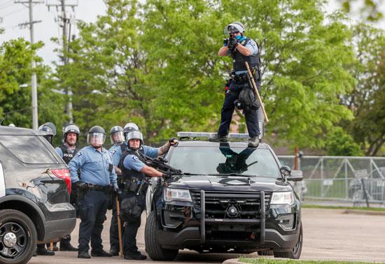 ضابط شرطة يصوب بندقية قبل إطلاق النار على الناس في المحطة الثالثة في قسم شرطة مينيابوليس للاحتجاج على وفاة جورج فلويد