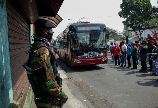 الحرس الوطنى البوليفى بجوار الحافلة قبل وصولها فنزويلا بعد إنقضاء الـ 14 يوم عزل طبى