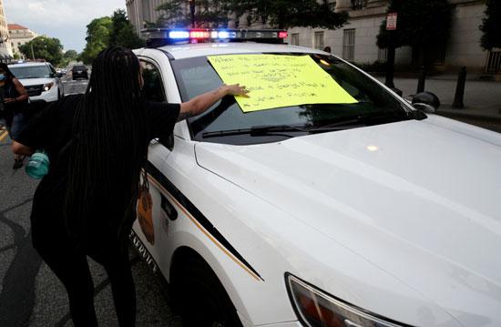 المحتجون يضعون لافتات على سيارات الشرطة