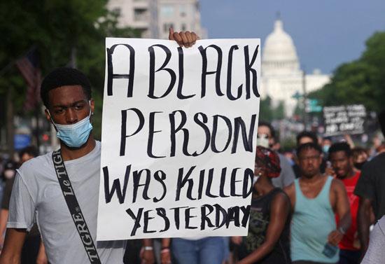 رجل يحمل لافتة ضد العنصرية