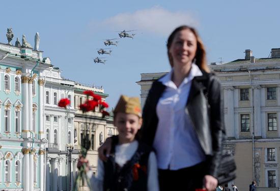 سيدة وأبنها و خلفهم طائرات الهليكوبتر خلال بدء العروض