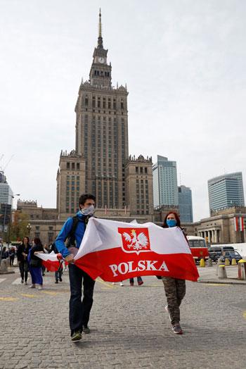 محتجون يرفعون علم بولندا