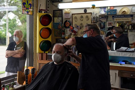 رجل يصفف شعره وآخر ينتظر خارج المحل