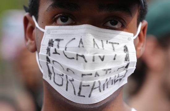 أحد المتظاهرين يضع شعارا على الكمامة خلال التظاهرة