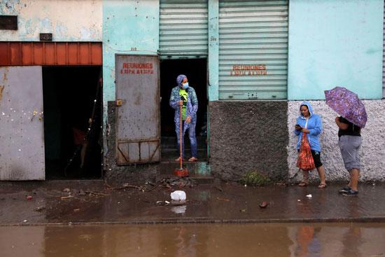 سيدة تزيل مياه الأمطار من داخل منزلها