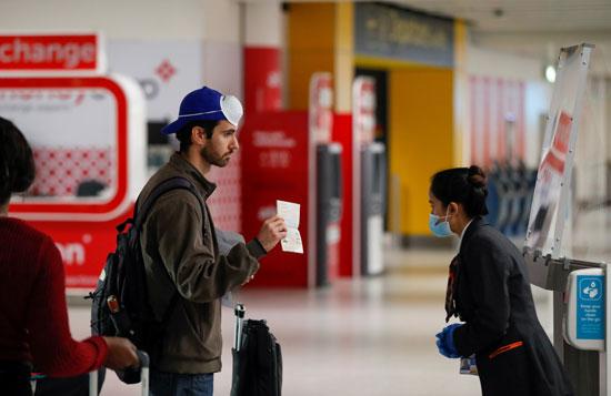 أحد الركاب يظهر جواز سفره لشرطة المطار