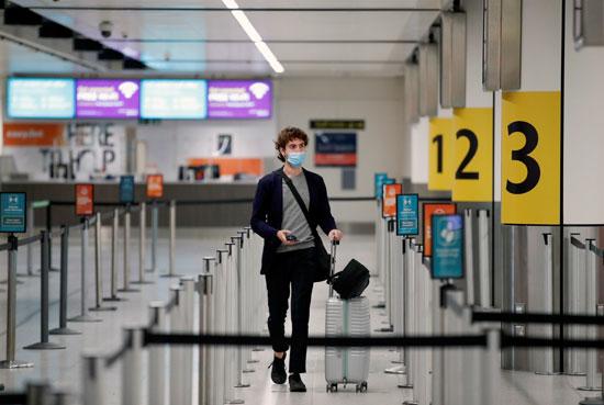 راكب يرتدى كمامة فى مطار جاتويك