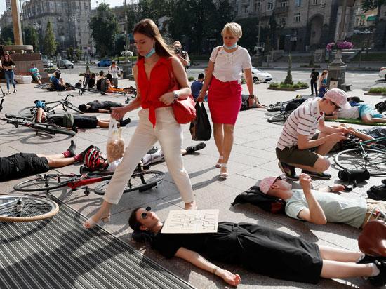 متظاهرة تضع لافتة خلال استلقائها على الأرض