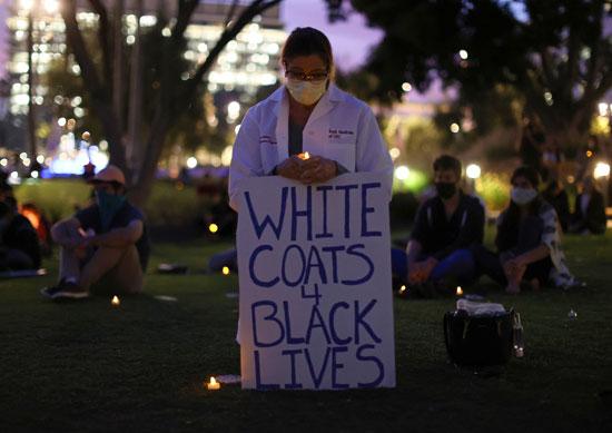 طبيبة تحمل لافتة مكتوب عليها معاطف بيضاء لحياة سوداء