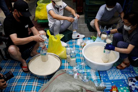 أفراد المجموعة يعبؤن الزجاجات بالأرز