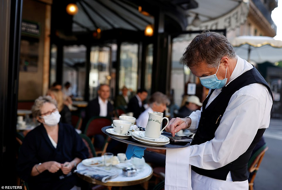 29114936-8379491-A_waiter_wearing_a_face_mask_serves_at_Cafe_de_Flore_as_restaura-a-19_1591096943634