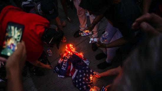المتظاهرون يشعلون علم ترامب بالقرب من مكان تجمعه مع مناصريه