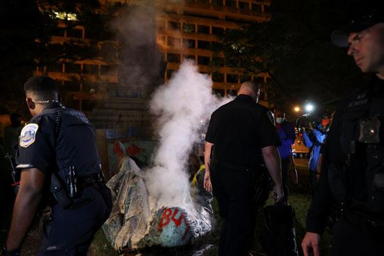 الشرطة تحاول اطفال النيران فى التمثال