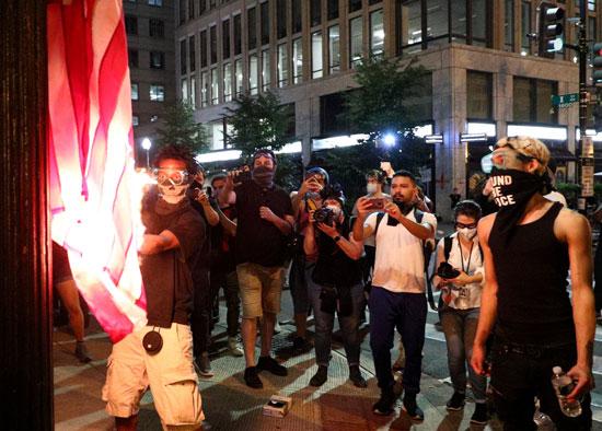 متظاهرون يحرقون علم أمريكا بواشنطن