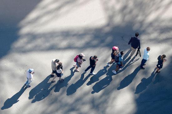 عدد من الاشخاص يصطفون أمام برج ايفل