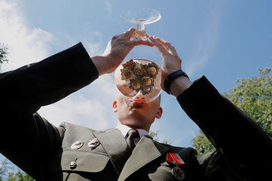 خريج يشرب الشمبانيا وهو يحتفل بعد حصوله على دبلوم في الأكاديمية العسكرية في روسيا البيضاء