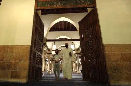 أب وابنه يغادران المسجد عقب الصلاة