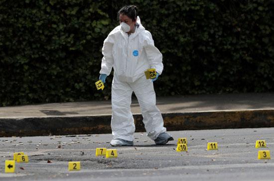 عناصر الأمن تعاين موقع محاولة اغتيال قائد شرطة مكسيكو سيتى