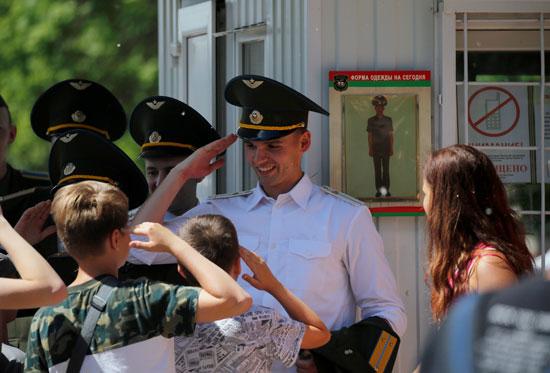 أطفال يحيون الخريجين بعد حفل الدبلوم في الأكاديمية العسكرية في روسيا البيضاء