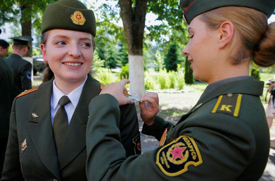 طالبة عسكرية تزيل ورقة نقدية بالدولار من حزام كتف لأحد الخريجين بعد حفل الدبلوم في الأكاديمية العسكرية في روسيا البيضاء