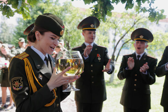 خريجة تشرب الشمبانيا وهي تحتفل بعد حصولها على دبلوم في الأكاديمية العسكرية في روسيا البيضاء