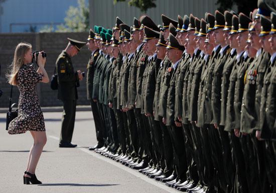 امرأة تلتقط صورًا للخريجين وهم يقفون في الطابور أثناء حصولهم على الدبلومات في الأكاديمية العسكرية في روسيا البيضاء