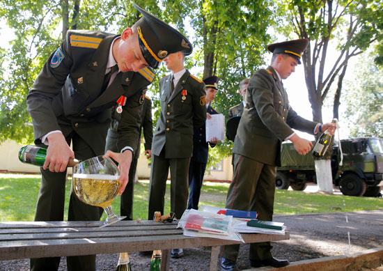 خريج يملأ كوبًا من الشمبانيا أثناء الاحتفال بعد حصولهم على الدبلومات في الأكاديمية العسكرية في روسيا البيضاء