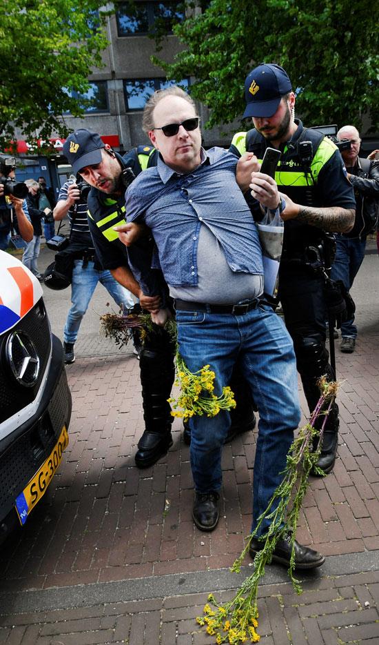ضباط الشرطة يحتجزون متظاهرًا خلال احتجاج ضد إجراءات التباعد الاجتماعى (1)