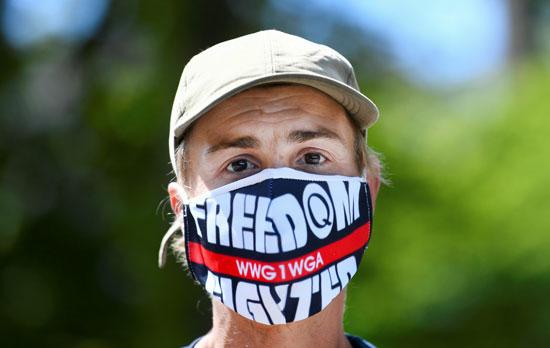 متظاهر يرتدي قناع وجه خلال احتجاج ضد تدابير الحكومة
