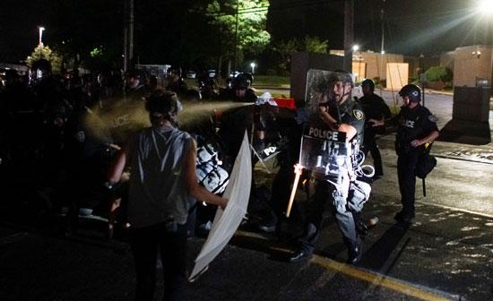 الشرطة تلقى غاز الفلفل على المتظاهرين