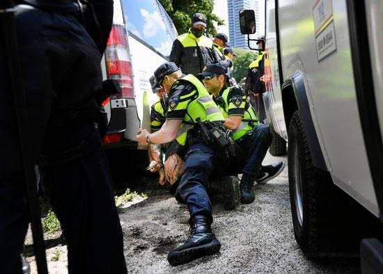 ضباط الشرطة يحتجزون متظاهرًا خلال احتجاج ضد إجراءات التباعد الاجتماعى (3)