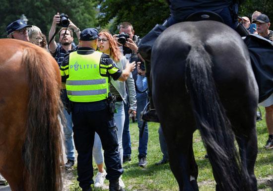 سيدة تتجادل مع ضابط شرطة أثناء احتجاج على تدابير التباعد