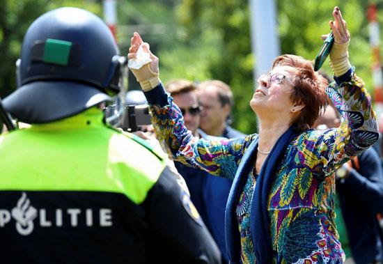 سيدة ترفع يديها أ أثناء مشاركتها في احتجاج ضد تدابير التسبب في فيروس كورونا