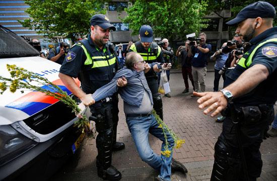 ضباط الشرطة يحتجزون متظاهرًا خلال احتجاج ضد إجراءات التباعد الاجتماعى (2)