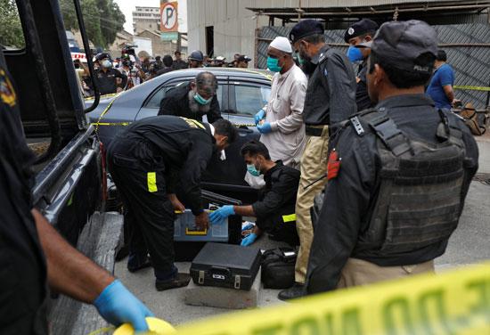 أعضاء وحدة مسرح الجريمة في شرطة كراتشي يستعدون لمسح موقع هجوم في بورصة باكستان في كراتشي