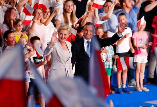 أندريه دودا رئيس بولندا وزوجته يوجهون التحيه لأنصارهم