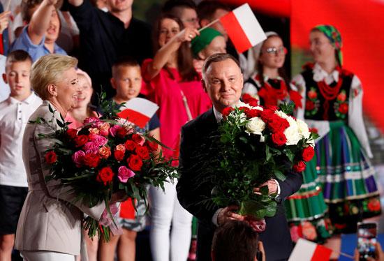 أندريه دودا رئيس بولندا وزوجته يحملان الورود
