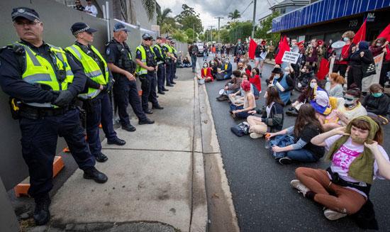 المتظاهرون يجلسون أمام الأمن  وفندق احتجاز طالبى اللجوء